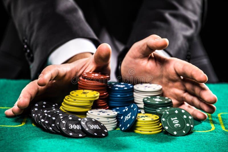Feche acima do jogador de pôquer com as microplaquetas na tabela verde do casino fotografia de stock royalty free