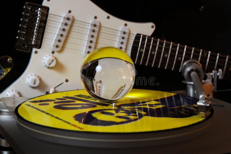 Feche acima do jogador de registro com vinil punk amarelo LP e a guitarra elétrica borrada de bola de vidro da esfera o und de cr foto de stock