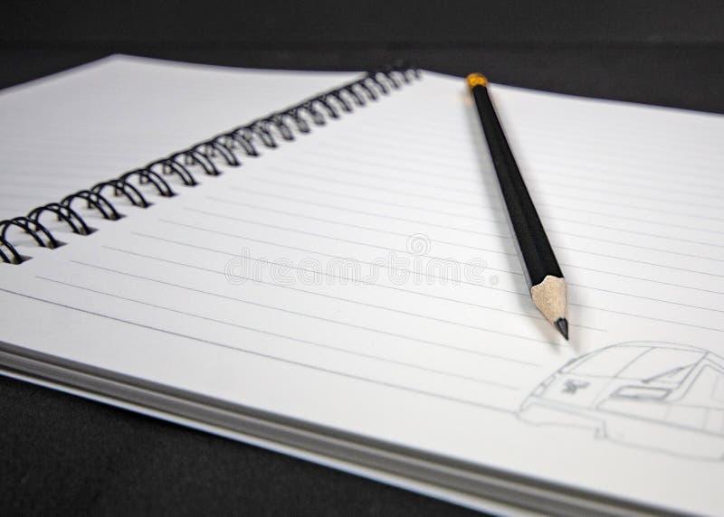 Feche acima do lápis de madeira preto que encontra-se em um caderno espiral fotografia de stock