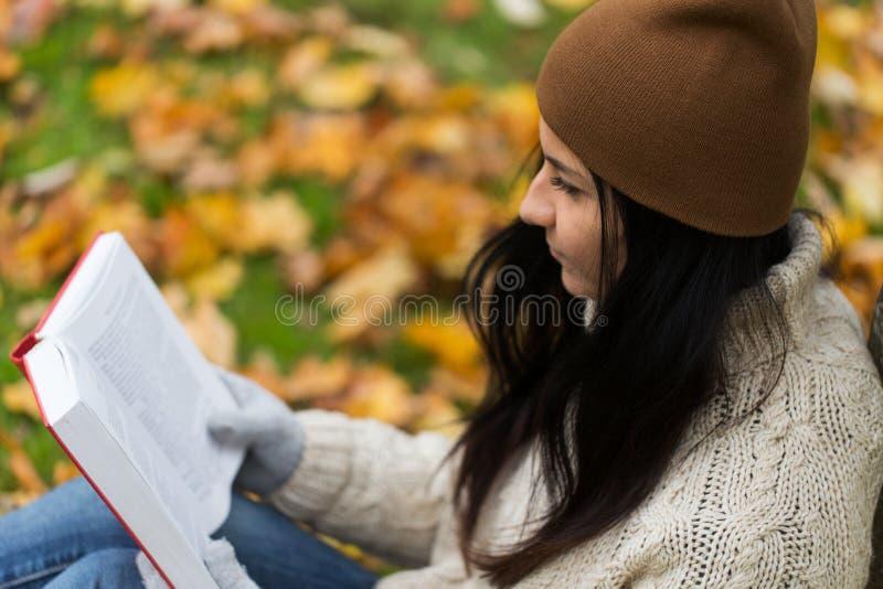 Feche acima do livro de leitura da mulher no parque do outono foto de stock royalty free