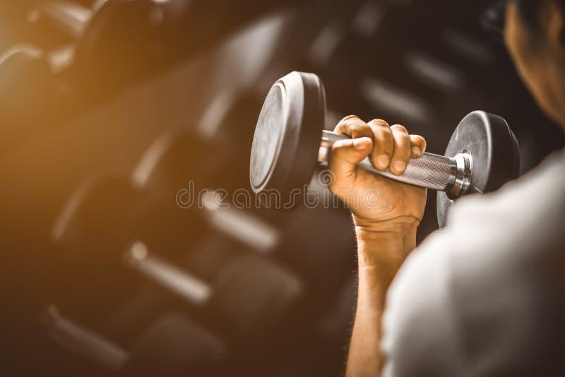 Feche acima do músculo grande caucasiano da mão nova do ajuste no sportswear Homem novo que guarda o peso durante uma classe do e imagem de stock royalty free