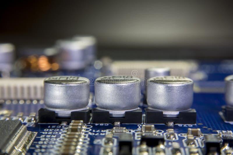 Feche acima do macro dos capacitores eletrolíticos de alumínio instalados sobre fotografia de stock