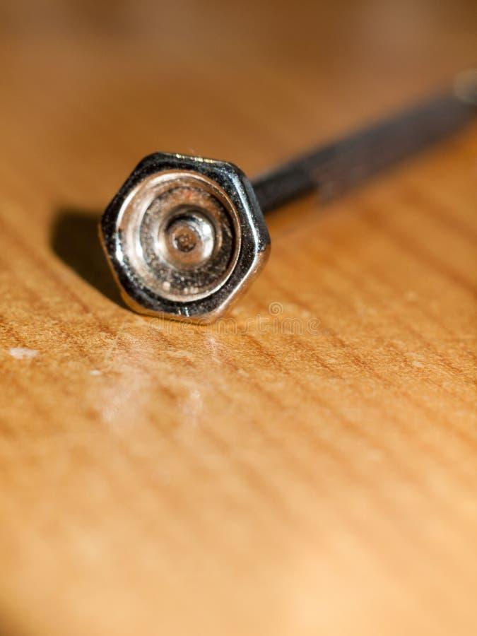 Feche acima do macro pequeno do metal da cabeça do parafuso do prego da chave de fenda fotografia de stock royalty free