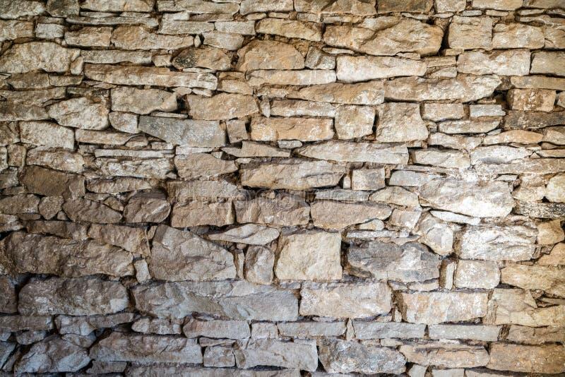 Feche acima do marrom liso velho e da textura cinzenta da parede de pedra Rochas mergulhadas em uma casa ou em uma construção Ext foto de stock royalty free