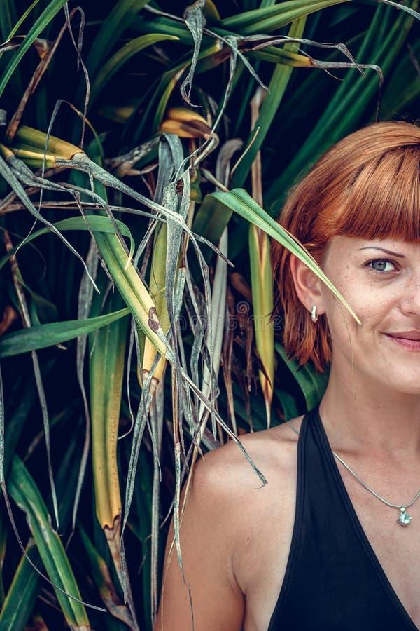 Feche acima do meio retrato da cara da mulher bonita nova nas folhas verdes para trás Ilha tropical Bali, Indonésia Bonito fotos de stock royalty free