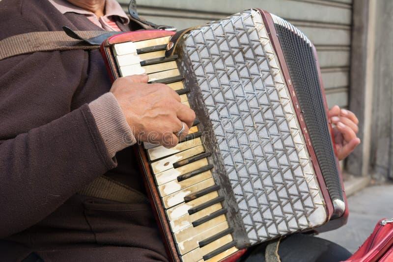 Feche acima do mendigo idoso Woman Playng um acordeão sujo no estreptococo imagem de stock royalty free
