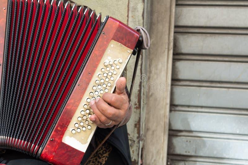 Feche acima do mendigo idoso Woman Playng um acordeão sujo no estreptococo foto de stock royalty free