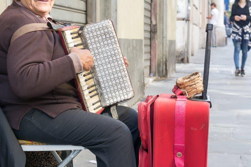 Feche acima do mendigo idoso Woman Playng um acordeão sujo no estreptococo foto de stock