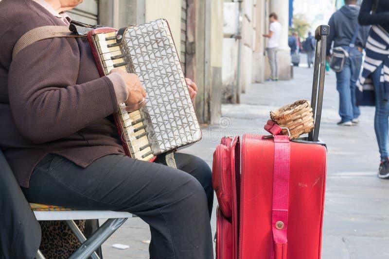 Feche acima do mendigo idoso Woman Playng um acordeão sujo no estreptococo imagem de stock