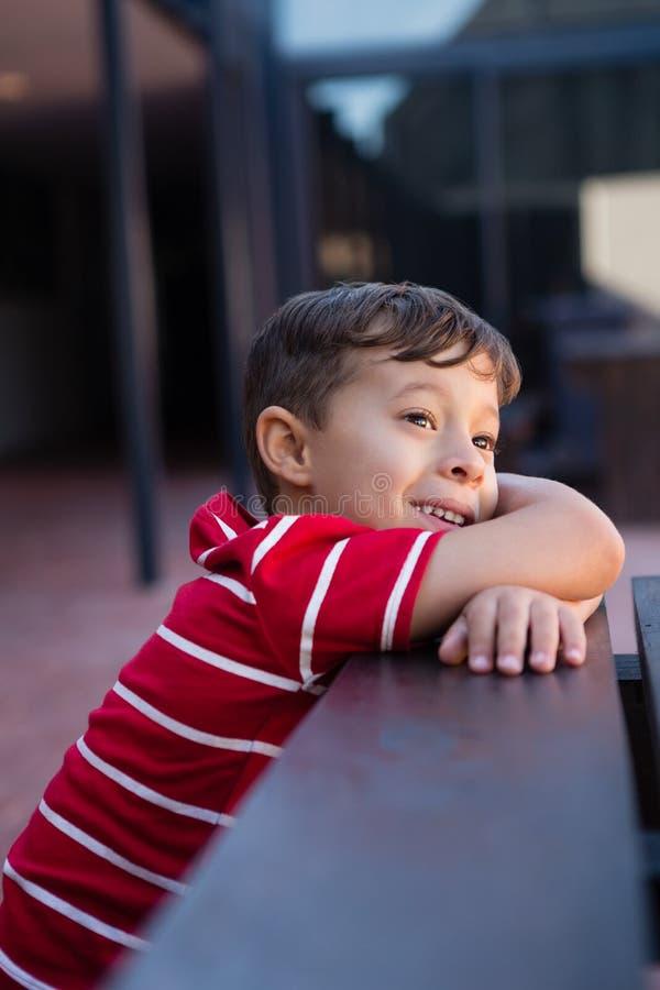 Feche acima do menino bonito que olha ausente ao inclinar-se na tabela imagem de stock royalty free
