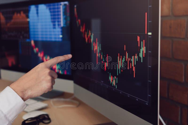 Feche acima do mercado de valores de ação do gráfico apontando e da análise do homem de negócios da mão no computador no escritór imagem de stock royalty free
