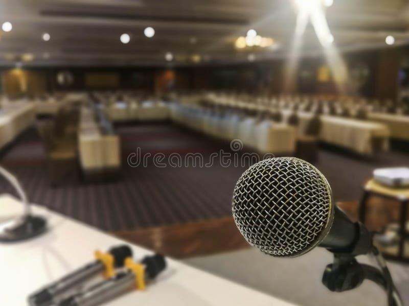 Feche acima do microfone em abstrato borrado do discurso na sala de seminário ou no fundo falador da luz da sala de conferências imagens de stock