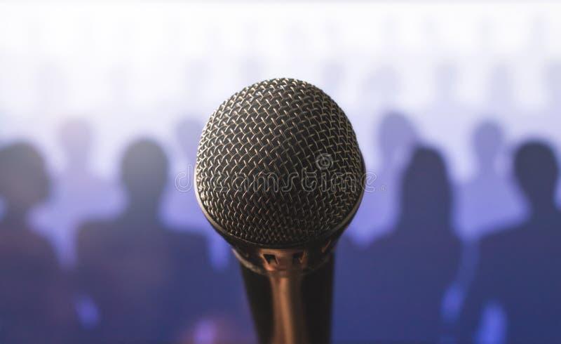 Feche acima do microfone na frente de uma audiência da silhueta foto de stock royalty free
