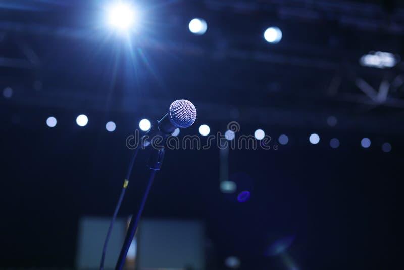 Feche acima do microfone na sala de concertos ou na sala de conferências com luzes frias no fundo imagens de stock