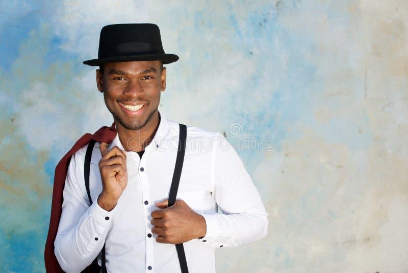Feche acima do modelo de forma masculino afro-americano novo de sorriso que levanta com suspensórios e chapéu pela parede fotografia de stock royalty free