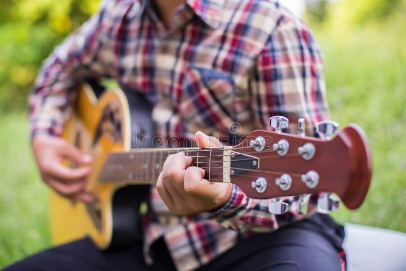 Feche acima do moderno que novo o homem praticou a guitarra no parque, feliz e aprecie jogar a guitarraajuste fotografia de stock