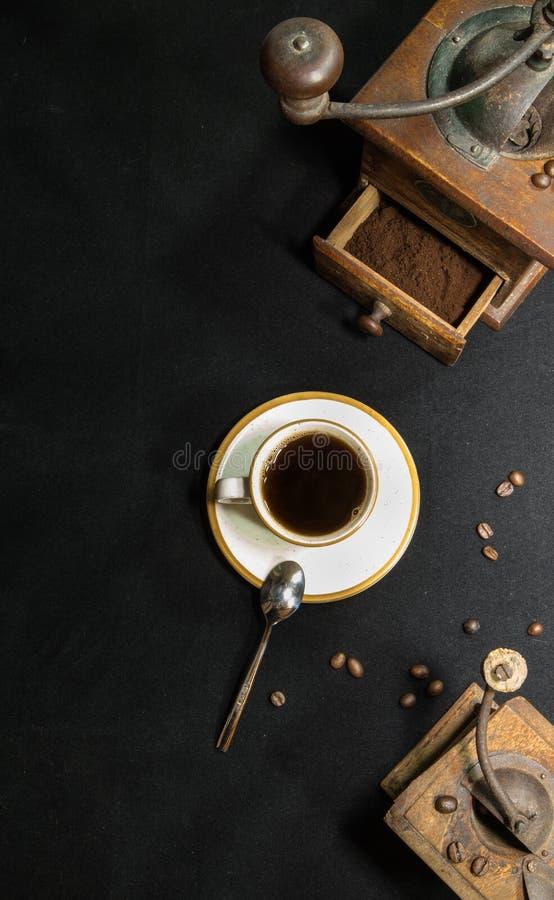 Feche acima do moedor retro do vintage velho com o copo da opinião superior de café preto e de feijões de café no fundo preto com fotos de stock