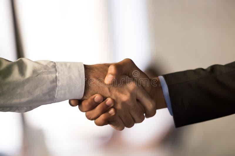 Feche acima do negócio de fechamento do aperto de mão masculino dos empregados fotografia de stock