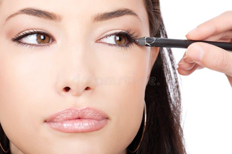 Feche acima do olhar de aplicar o lápis cosmético imagens de stock royalty free