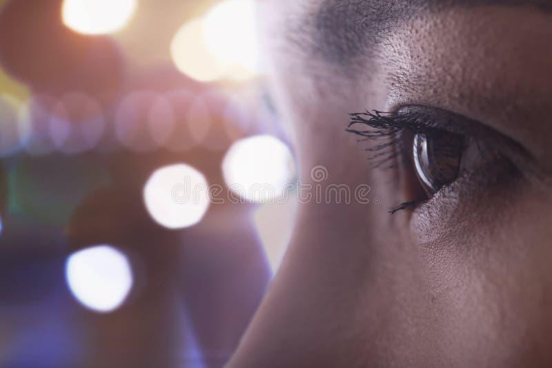 Feche acima do olho da mulher, vista lateral, brilhante fora das luzes do foco no fundo imagens de stock royalty free