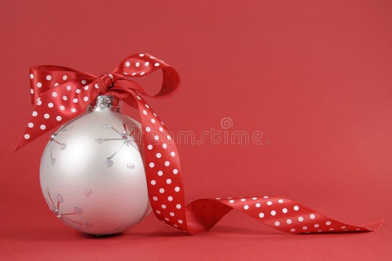 Feche acima do ornamento bonito da árvore do White Christmas com a fita vermelha do às bolinhas no fundo vermelho imagem de stock royalty free