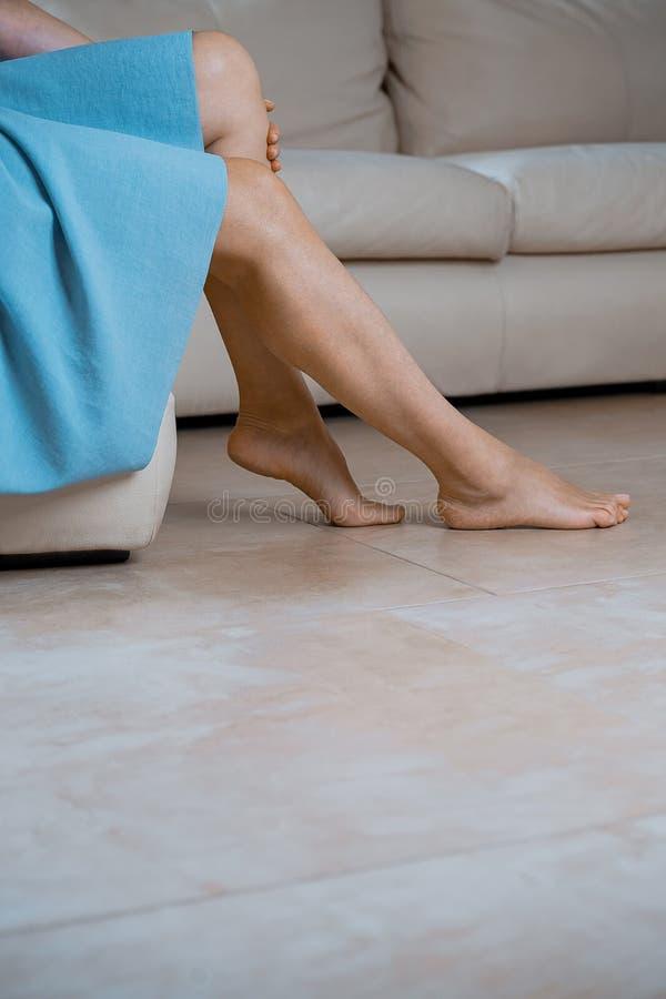 Feche acima do os pés fêmeas perfeitos Mulher que aplica o moisturizer C fotografia de stock