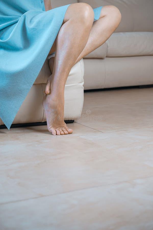 Feche acima do os pés fêmeas perfeitos Mulher que aplica o moisturizer C imagem de stock royalty free
