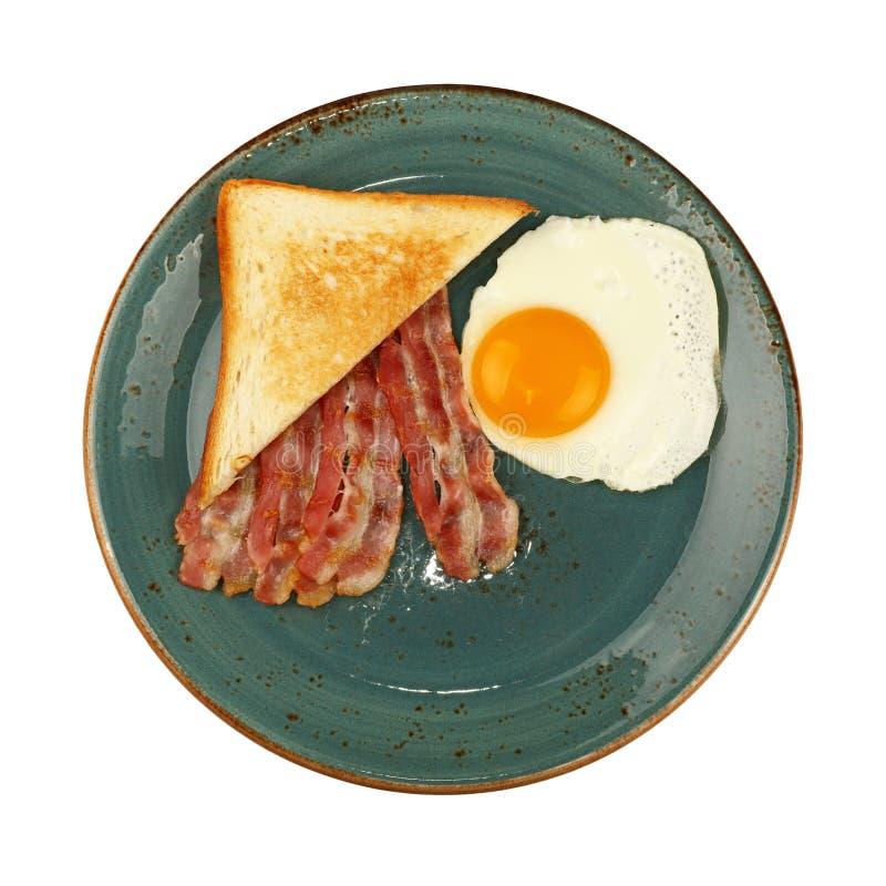 Feche acima do ovo, do brinde e do bacon na placa azul fotografia de stock