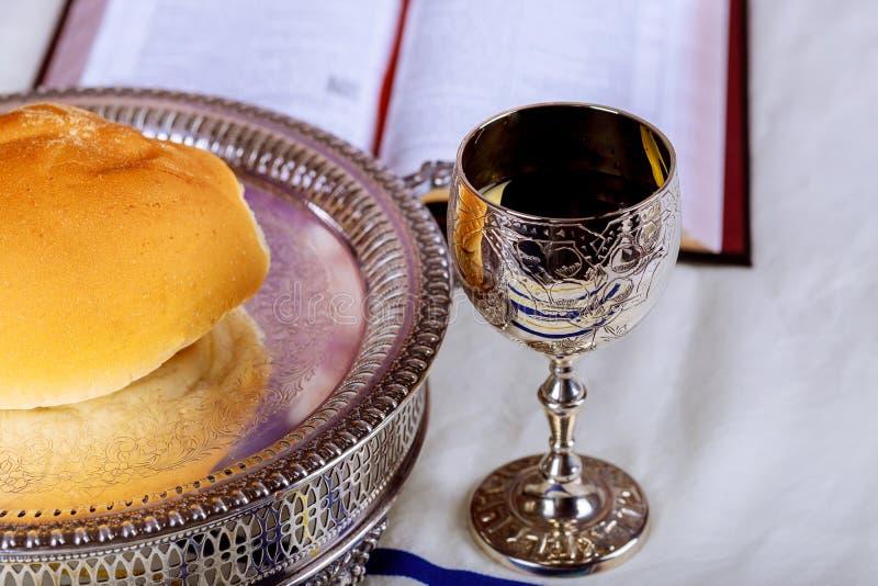 Feche acima do pão e de um copo do vinho tinto na tabela de madeira para o comunhão, conceito cristão para o lembrete de Jesus imagem de stock royalty free