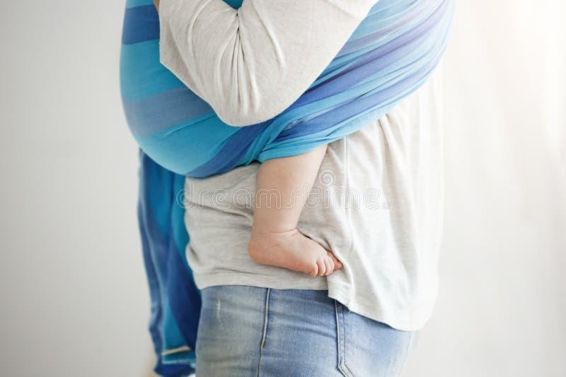 Feche acima do pé bonito das crianças Da mãe huggs novos maciamente seu filho Cena tocante do amor de maternidade Família imagem de stock royalty free