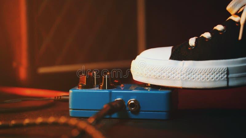 Feche acima do pé do guitarrista que pressiona o pedal O músico usa a máquina do laço do efeito da música Homem nas sapatilhas na fotografia de stock royalty free