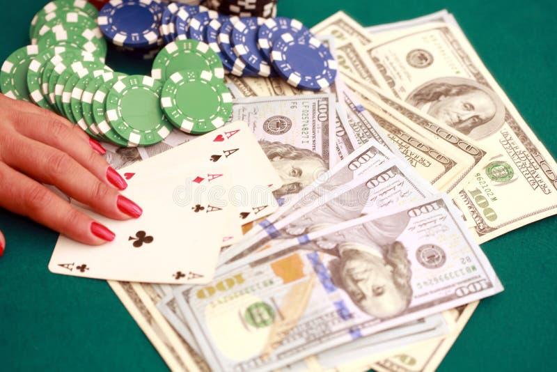 Feche acima do pôquer em cartões e em microplaquetas de jogo da mão do ` s da mulher no gre imagem de stock royalty free