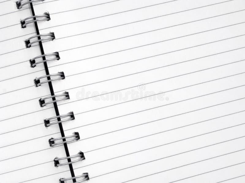 Feche acima do papel alinhado branco em um bloco de notas espiral. imagem de stock royalty free
