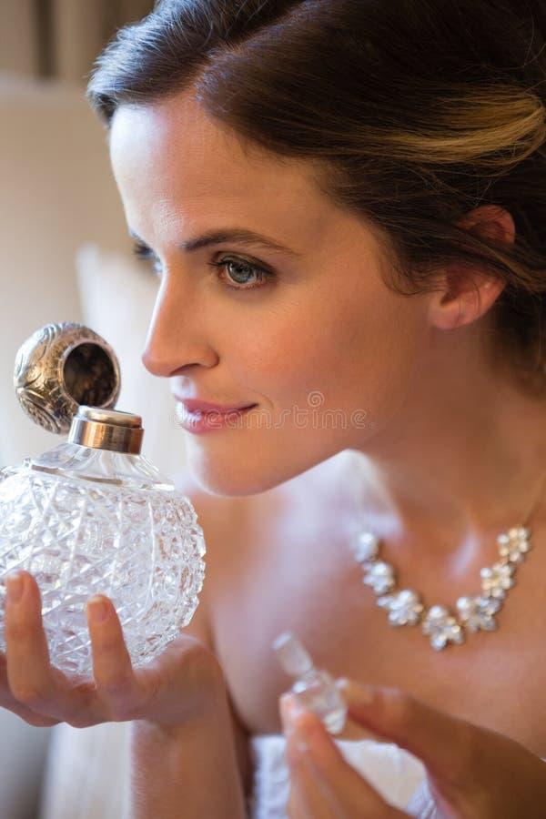 Feche acima do perfume de cheiro da noiva bonita ao sentar-se na poltrona imagens de stock royalty free