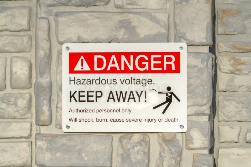 Feche acima do perigo que a tensão perigosa mantém afastado o sinal afixado em uma superfície cinzenta imagens de stock royalty free