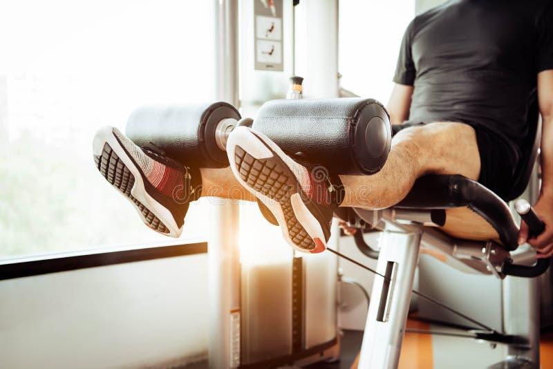 Feche acima do peso de levantamento do homem por dois pés para esticar o músculo no gym da aptidão no fundo privado do condomínio imagem de stock