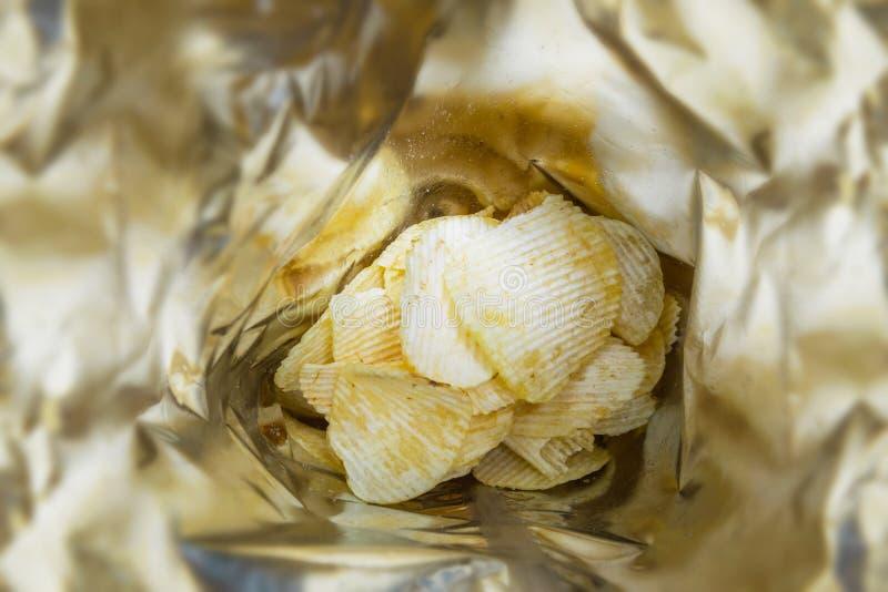 Feche acima do petisco fritado das microplaquetas de batata da vista superior em um saco de plástico foto de stock