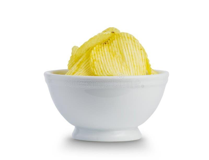 Feche acima do petisco fritado das microplaquetas de batata na bacia branca no fundo branco, comida lixo fotos de stock