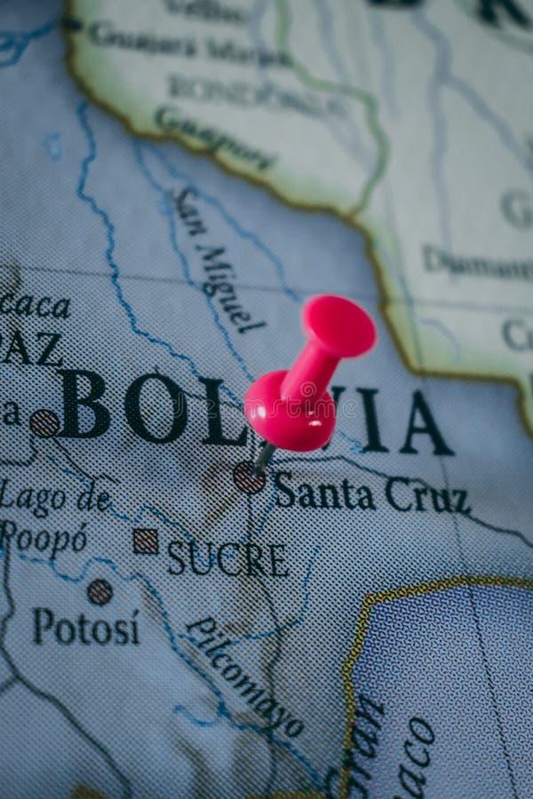 Feche acima do pino de Bolívia apontou no mapa do mundo com um percevejo cor-de-rosa foto de stock