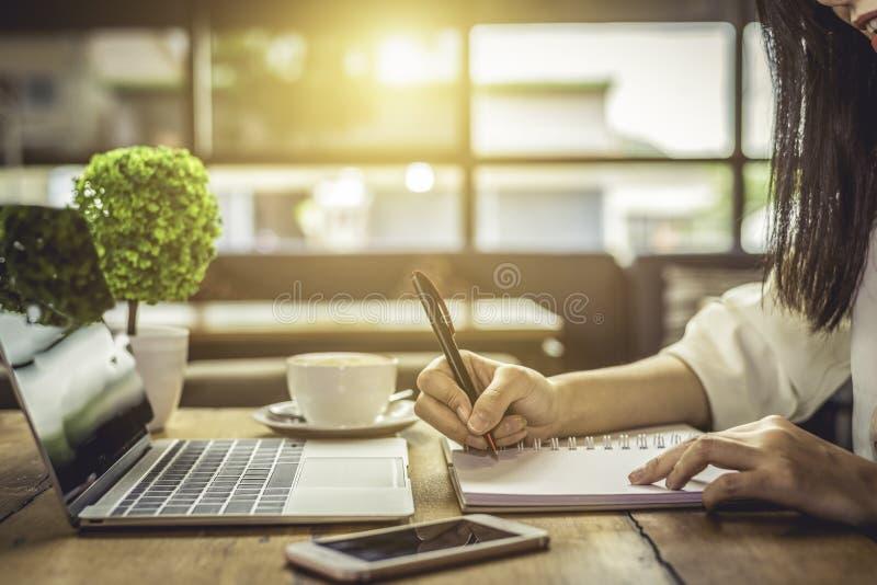 Feche acima do planeamento de projeto do negócio da escrita da mão da mulher na nota foto de stock royalty free