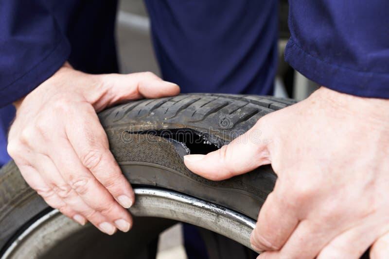 Feche acima do pneumático de Examining Damaged Car do mecânico fotos de stock