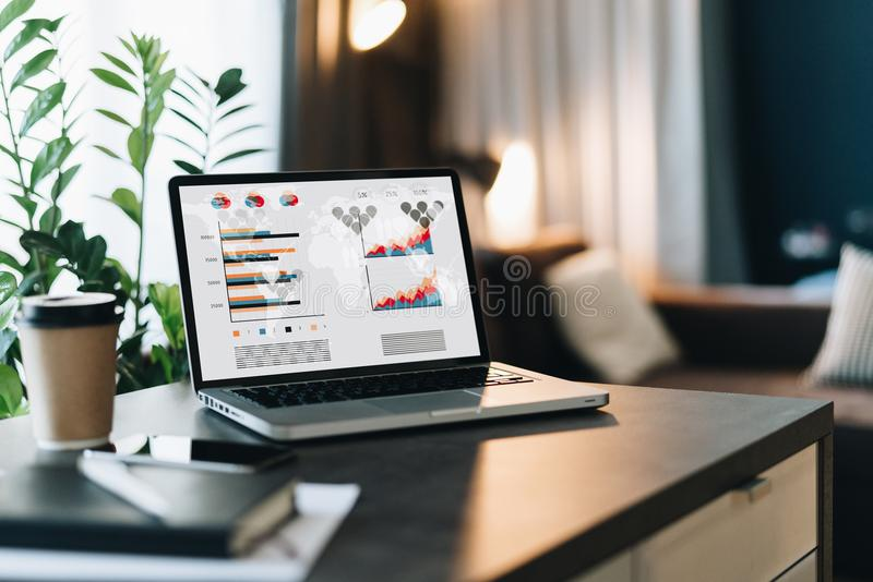 Feche acima do portátil com gráficos, cartas, diagramas, programação na tela na tabela na sala vazia workplace Mercado em linha fotografia de stock royalty free