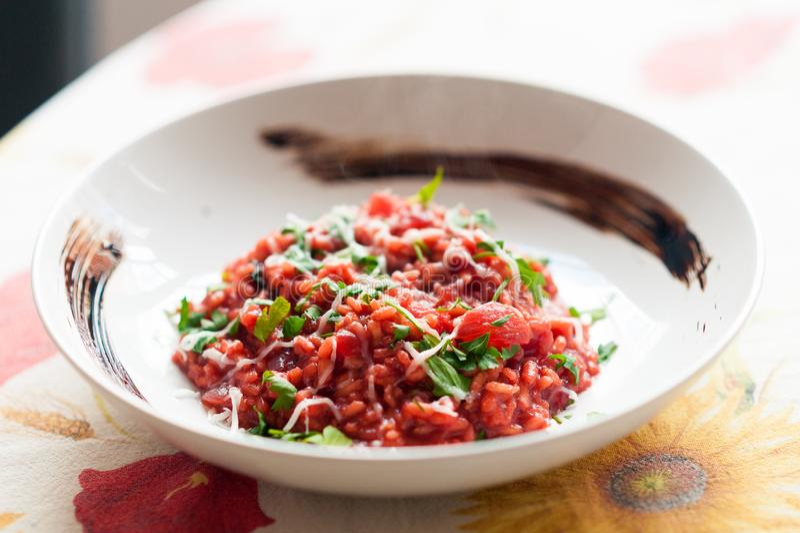 Feche acima do prato gourmet vermelho italiano do risoto com beterraba, salsa, queijo e vinagre balsâmico de modena na placa bran imagens de stock royalty free