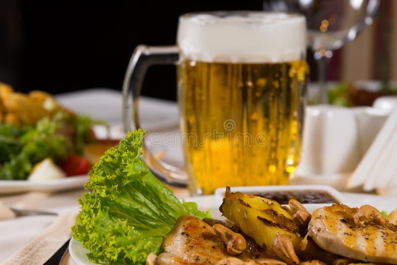 Feche acima do prato principal Meaty com a caneca de cerveja fotos de stock
