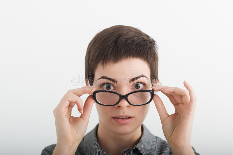 Feche acima do professor fêmea ou do estudante engraçado novo surpreendido restrito nos vidros isolados no fundo branco, olhando  imagem de stock