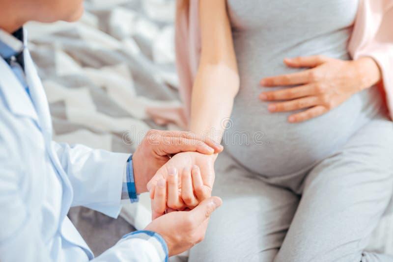 Feche acima do pulso de medição do doutor da mulher gravida foto de stock