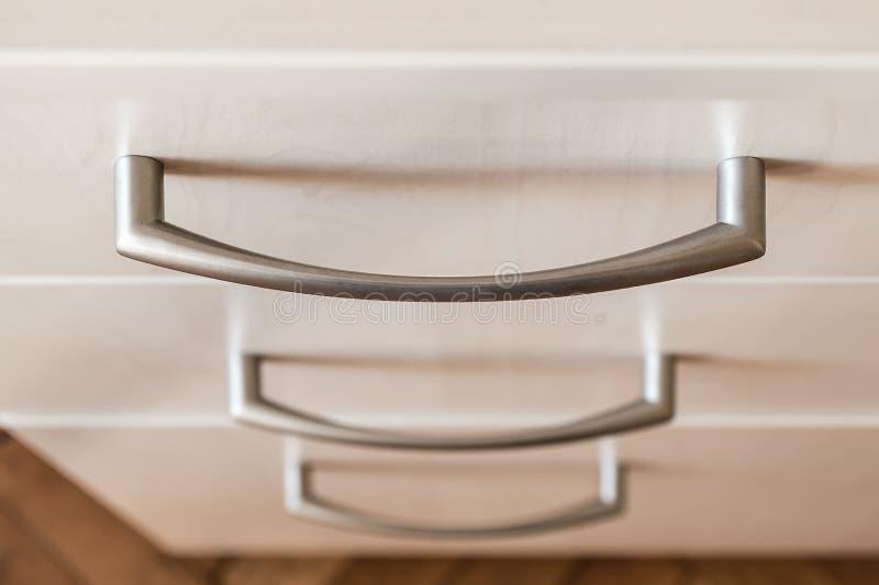 Feche acima do punho do metal de uma gaveta Caixa de gavetas de madeira moderna da cor clara Conceito da mobília minimalista da c foto de stock royalty free