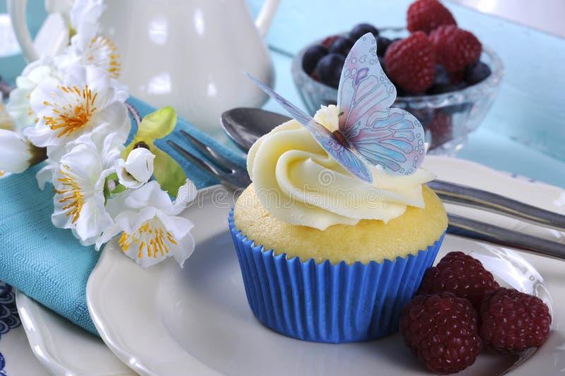 Feche acima do queque delicioso com a decoração da bolacha da borboleta no ajuste azul da bandeja do aqua do vintage fotos de stock royalty free