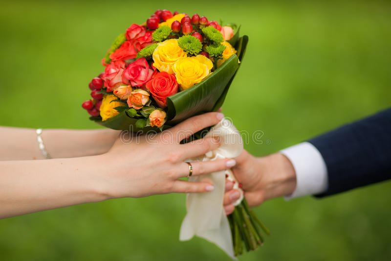 Feche acima do ramalhete bonito de flores frescas Mãos do homem e da mulher noiva feliz, noivo sobre o fundo do parque do verde d fotografia de stock royalty free