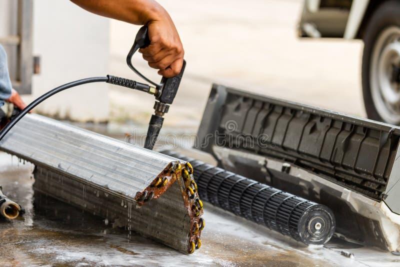 Feche acima do reparador que lava o condicionador de ar interno sujo dos compartimentos, molde limpo da equipe técnica no condici imagens de stock royalty free